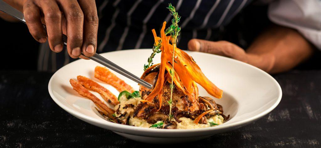 Indian oriental chef blue apron decorating fine dinning chicken dish restaurant kitchen black background